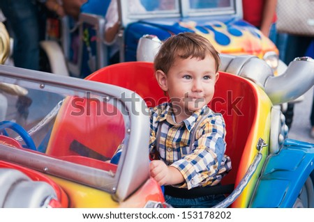 Little boy riding a car in amusement park - stock photo