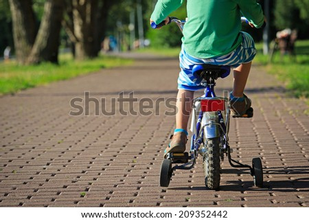 little boy riding bike in summer park - stock photo