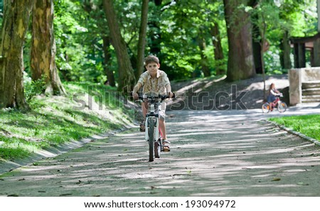 Little boy riding on bike in the park at sunny day - stock photo