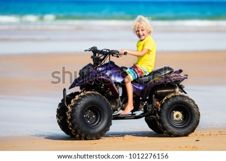 Little boy riding quad bike on tropical beach. Cute blond curly child on quadricycle. All-terrain vehicle ride. Motor cross sports on ocean sand dune. Kids summer vacation activity. Off road race.