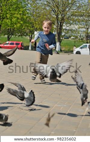 Little boy running among pigeons - stock photo