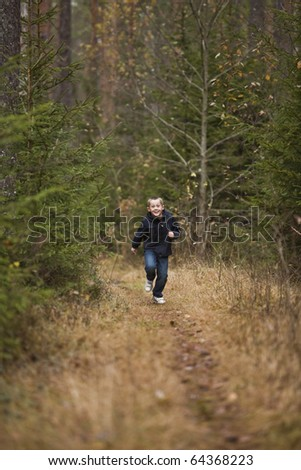 Little Boy running in the forest - stock photo