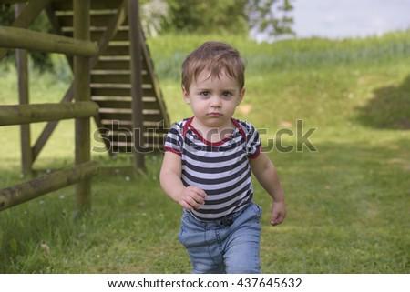 Little boy running in the garden - stock photo