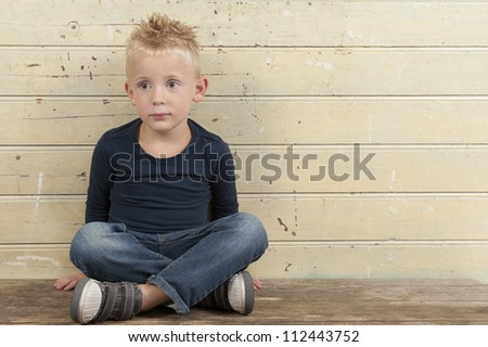 little boy seated against an old wooden door - stock photo