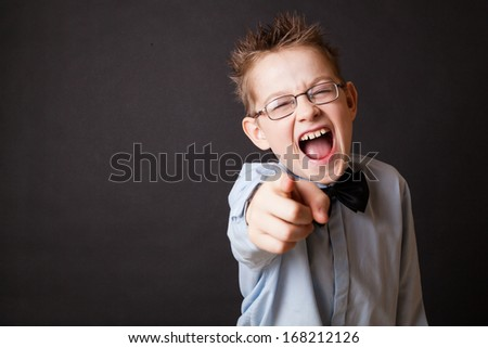 Little boy shouting and pointing out with his finger to the camera - stock photo