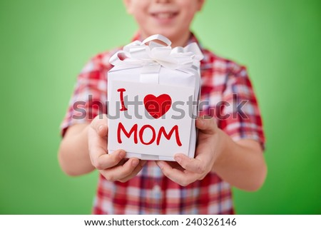 Little boy showing gift for mother with note - stock photo