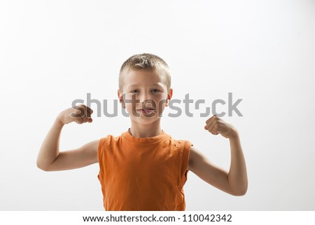 Little boy showing his muscles, white background - stock photo