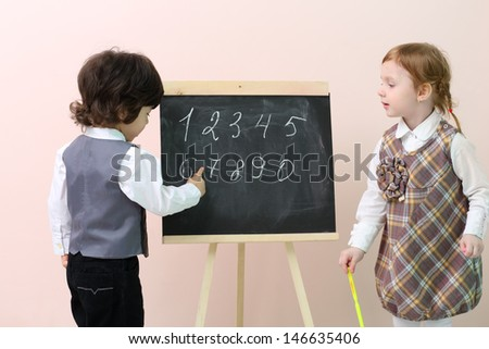 Little boy shows by finger figures at chalkboard for cute girl in studio. - stock photo