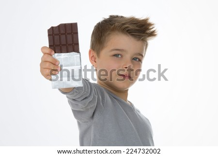 little boy shows his favorite chocolate bar - stock photo