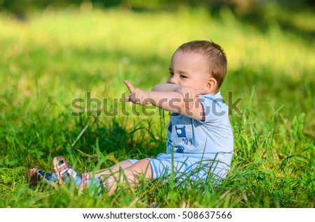 Little boy shows his index fingers in opposite directions in the summer in the park