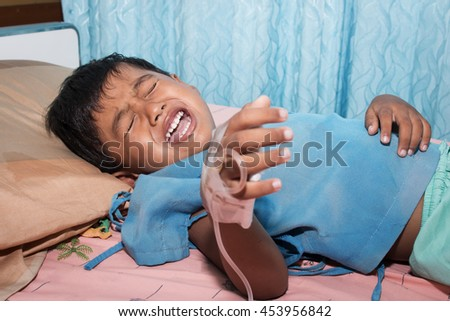 Little boy sick and crying on patient bed - stock photo