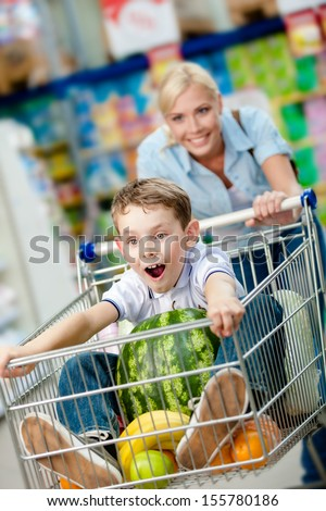Little boy sits in the shopping trolley with watermelon and other products while mother drives it - stock photo
