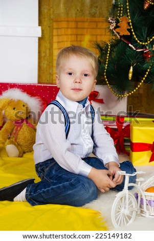 Little boy sits near the Christmas decorated fir-tree - stock photo