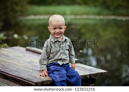 Little boy sits on a bridge by the pond