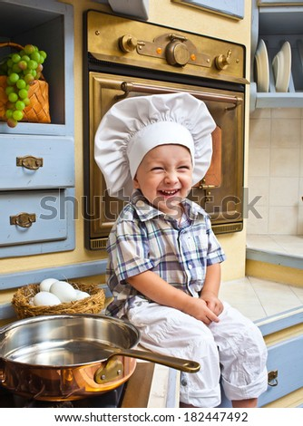 little boy sits on a kitchen table and plays the cook - stock photo