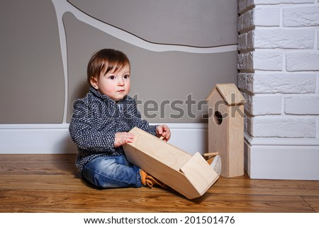 Little boy sits on the floor and playing with starling house