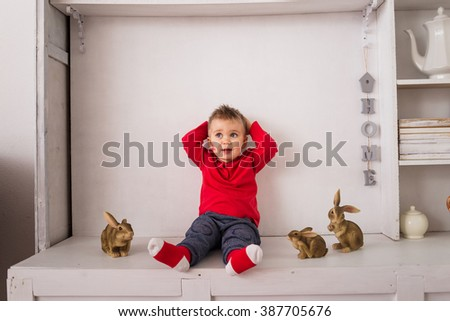 Little boy sits on the white kitchen buffet and plays with ceramic rabbits