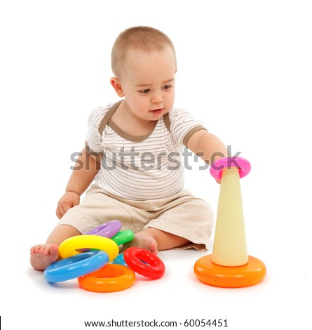 Little boy sitting and playing with colorful plastic torus toy - stock photo