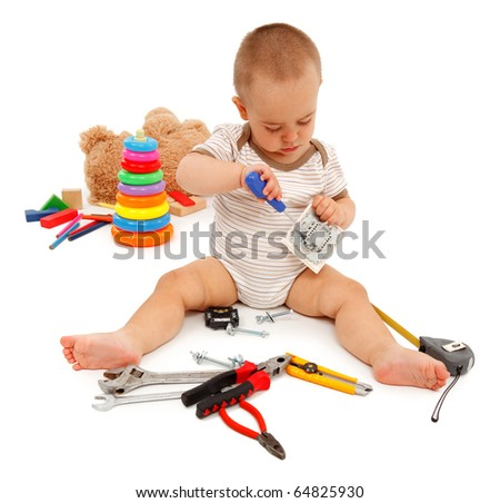 Little boy sitting and playing with real tools instead of his toys - stock photo