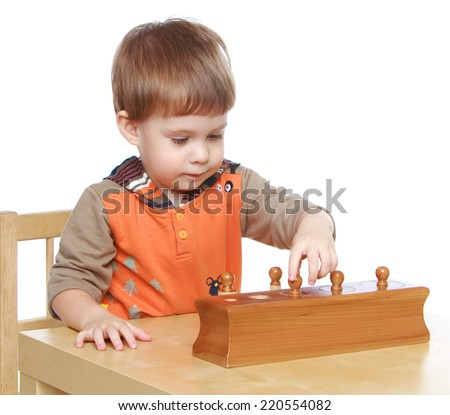 Little boy sitting at a table with educational toys, Montessori classroom isolated on white background.The concept of development of the child, the child's upbringing. - stock photo