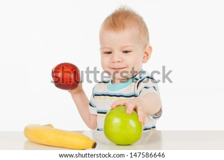 Little boy sitting at a table with fruit, on a gray background - stock photo