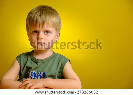 Little boy sitting at table on yellow background - stock photo