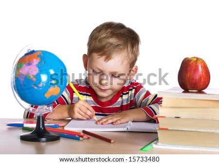 Little boy sitting by his desk - stock photo