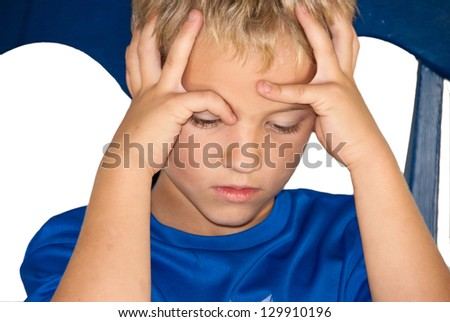 Little boy sitting in a chair pouting with this hands on his head and frown on his face. - stock photo