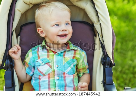little boy sitting in a stroller. baby for a walk in a stroller
