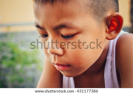 Little Boy sitting  in park. Loneliness, melancholy, Stress Dark Tone Child Upset problem concept for bullying,Sad Little boy worried  - stock photo
