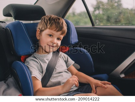 little boy sitting in safety car seat - stock photo