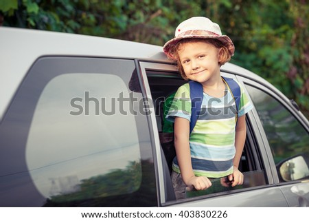 Little boy sitting in the car at the day time. Concept of happy life. - stock photo