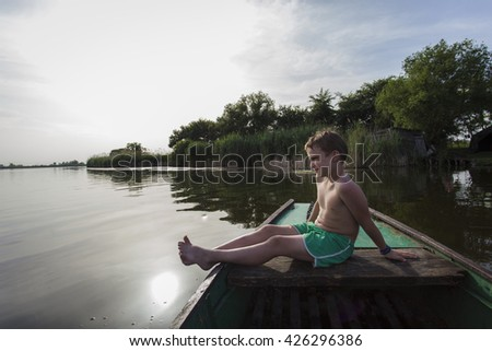 Little boy sitting on a boat on a river with arms up. Sunlight behind him.