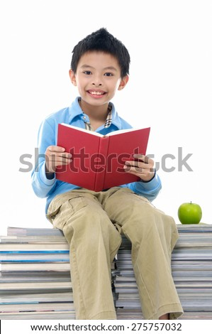little boy sitting on a pile of books  - stock photo