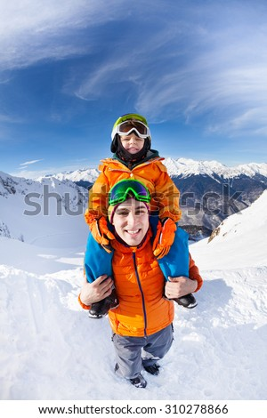 Little boy sitting on fathers shoulders on top of he mountain  - stock photo
