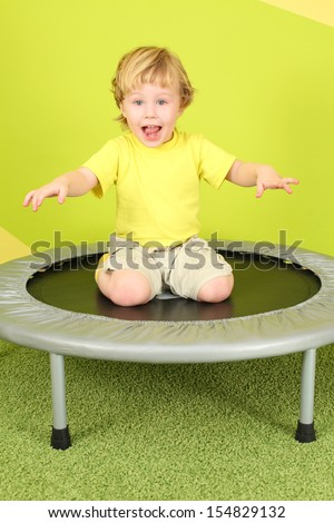 Little boy sitting on his lap on a small trampoline, his arms outstretched - stock photo
