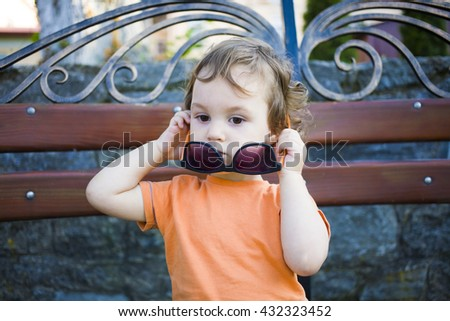 Little boy sitting on the bench and tries on the glasses of his mother.