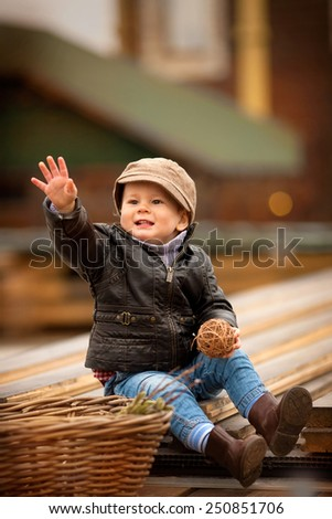 little boy sitting on the boards and throw the ball - stock photo