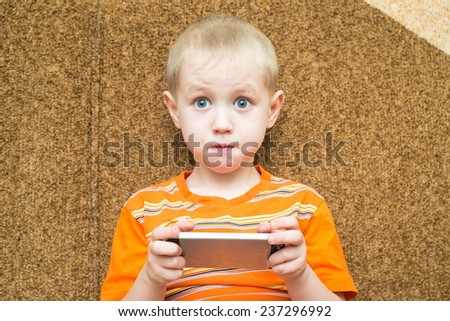 Little boy sitting on the couch with surprised eyes and holding a smartphone - stock photo
