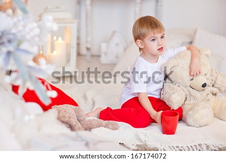 Little boy sitting on the floor near the fireplace and Christmas tree. Christmas Eve. New Year. Festive mood.