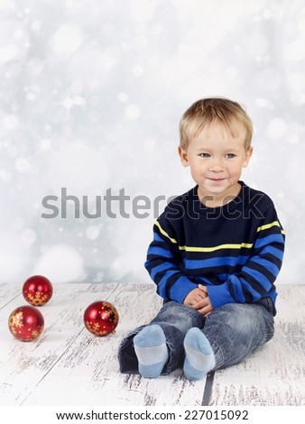 Little boy sitting on the floor with christmas balls - stock photo