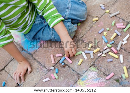 Little boy sitting on the pavement with colorful chalk - stock photo