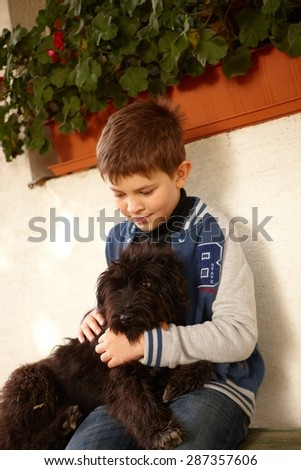 Little boy sitting outdoors hugging black dog. - stock photo