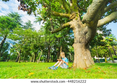 Little boy sitting under big tree and reading book.