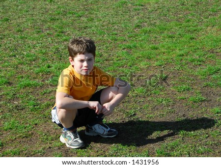 Little boy sitting upset on a soccer field after losing a game