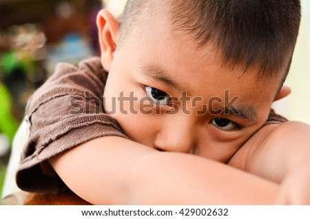 Little boy sitting with sadness at home.Close-up face of a child with the crossed arms crying and looking at the camera - stock photo