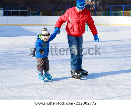 little boy skating with parent, first skating lesson - stock photo