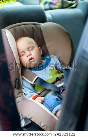 little boy sleeping in a car seat