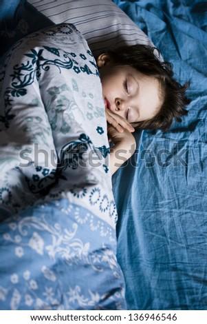 little boy sleeping in bed - stock photo