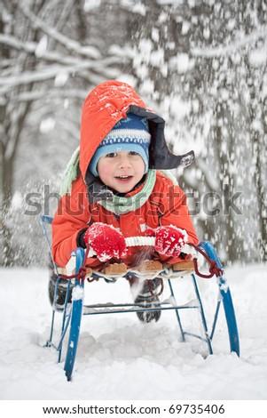Little boy sliding in the snow - stock photo